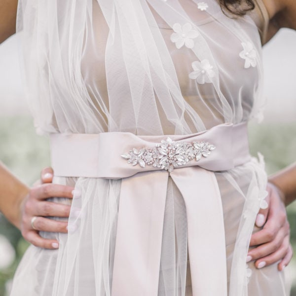 Cultural woman is wearing an unique designed rosé belt embroidered with crystal on the online boutique of Maison M'Elise
