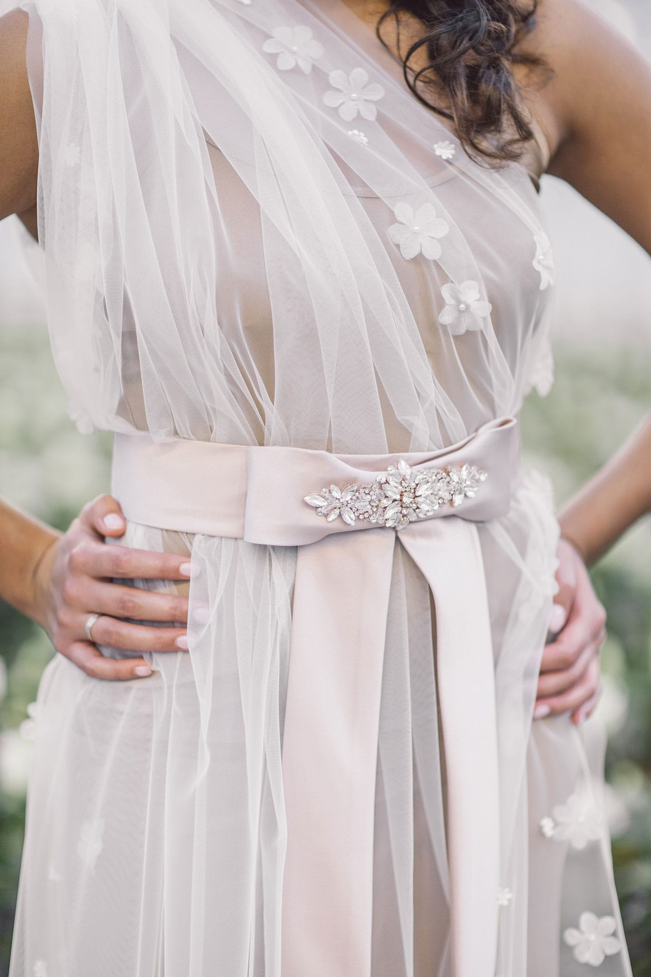 Cultural woman is wearing an unique designed rosé belt embroidered with crystals from the online boutique of Maison M'Elise