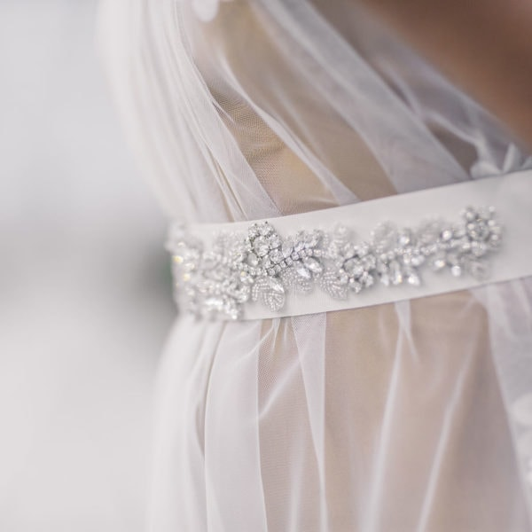 Woman wearing an unique designed wihite belt embroidered with crystals on the online boutique of Maison M'Elise