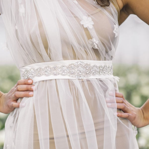 Cultural woman with hands on her hips wearing an unique designed white satin belt embroidered with crystals from the online boutique of Maison M'Elise