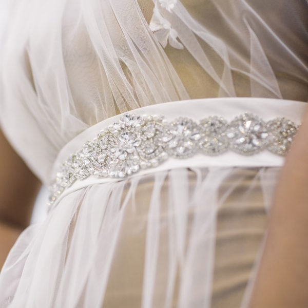Cultural wearing an unique designed white satin belt embroidered with crystals from the online boutique of Maison M'Elise