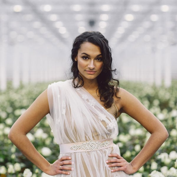 Cultural woman with hands on her hips standing in a room full of white roses is wearing a sustainable handmade rose golden satin belt around her waist of Maison M'Elise
