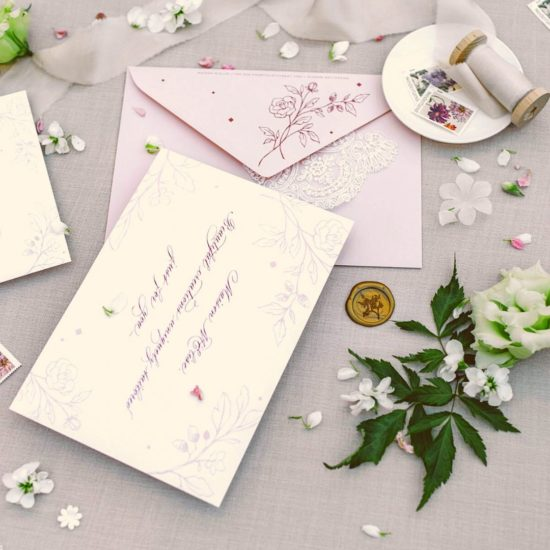 Decorated canva with sustainable rose and white wedding invitation letters of Maison M'Elise and white flowers