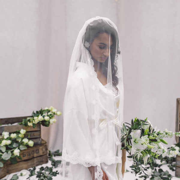 Cultural woman standing in front of beige cloths with wooden boxes holding a bouquet is wearing a white satin kimono, white satin nightgown and satin bridal spanish lace veil uniquely designed by Maison M'Elise