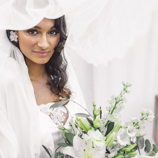 Cultural bride holding a bridal bouquet is wearing an unique designed white satin kimono, bridal veil, and white satin nightgown by Maison M'Elise