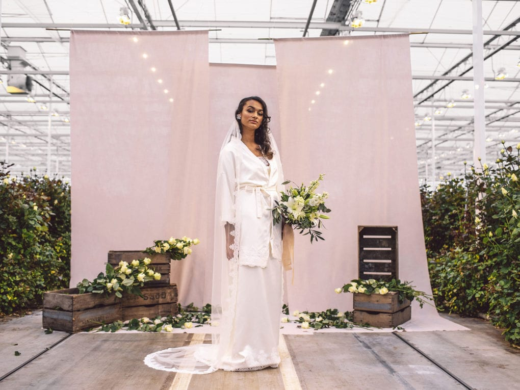 cultural bride standing in front of a beige cloths in a rosary holding a bridal bouquet is wearing an unique designed white satin nightgown, white satin kimono, and a spanish lace veil by Maison M'Elise