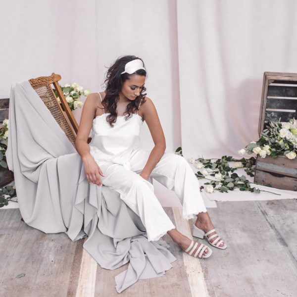Cultural woman seated on a wooden chair is wearing a sustainable handmade white satin pyjama set with white satin sleeping mask and nude sandals