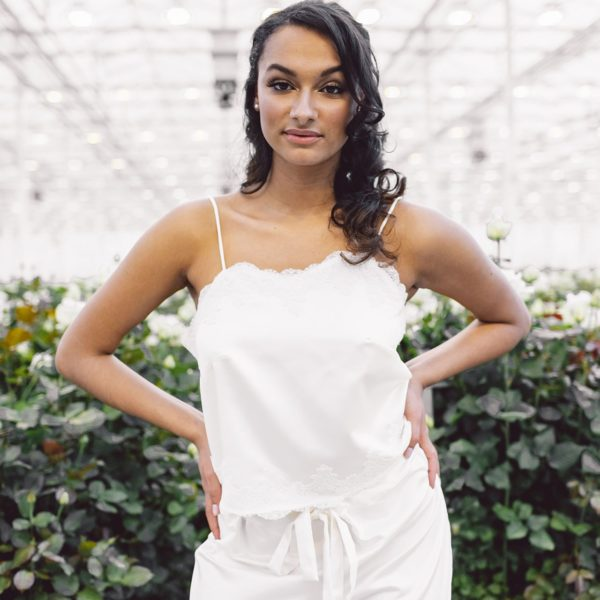 Cultural woman with hands on hips standing in rosary is wearing a sustainable white satin pyjama set designed by Maison M'Elise
