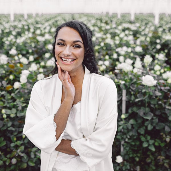 smiling cultural woman in a rosary wearing an unique designed white satin top and white satin kimono by Maison M'Elise