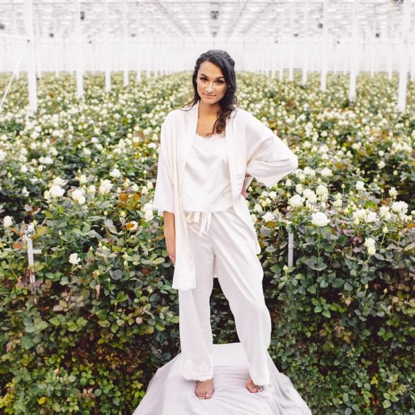 Cultural woman with one hand on hips is standing in front of room full of white roses wearing sustainble white kimono and white pyjama set of Maison M'Elise