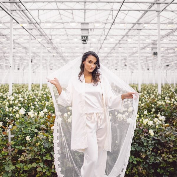 Cultural woman standing in front of room full of white roses wearing an unique handmade bridal veil, white kimono and pyjama set from the online boutique of Maison M'Elise