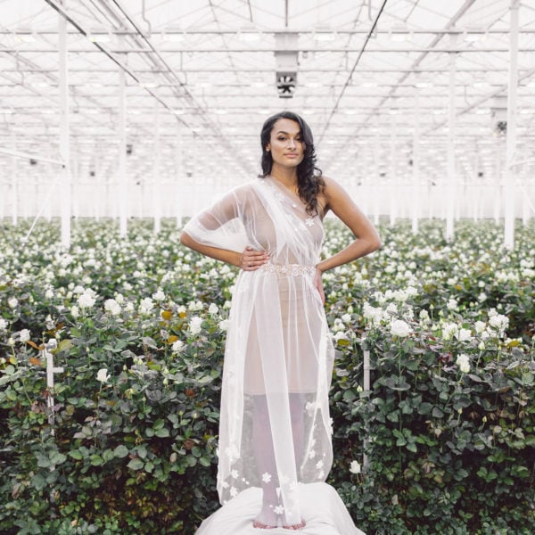 Cultural woman with hands on her hips standing in a room full of white roses is wearing a sustainable designed gold crystal belt around her waist of Maison M'Elise