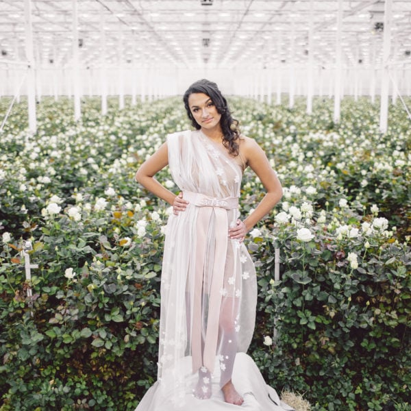 Cultural woman with hands on hips standing in a room full of white roses is wearing an unique designed rosé satin belt and a bow, embroidered with crystals from the online boutique of Maison M'Elise
