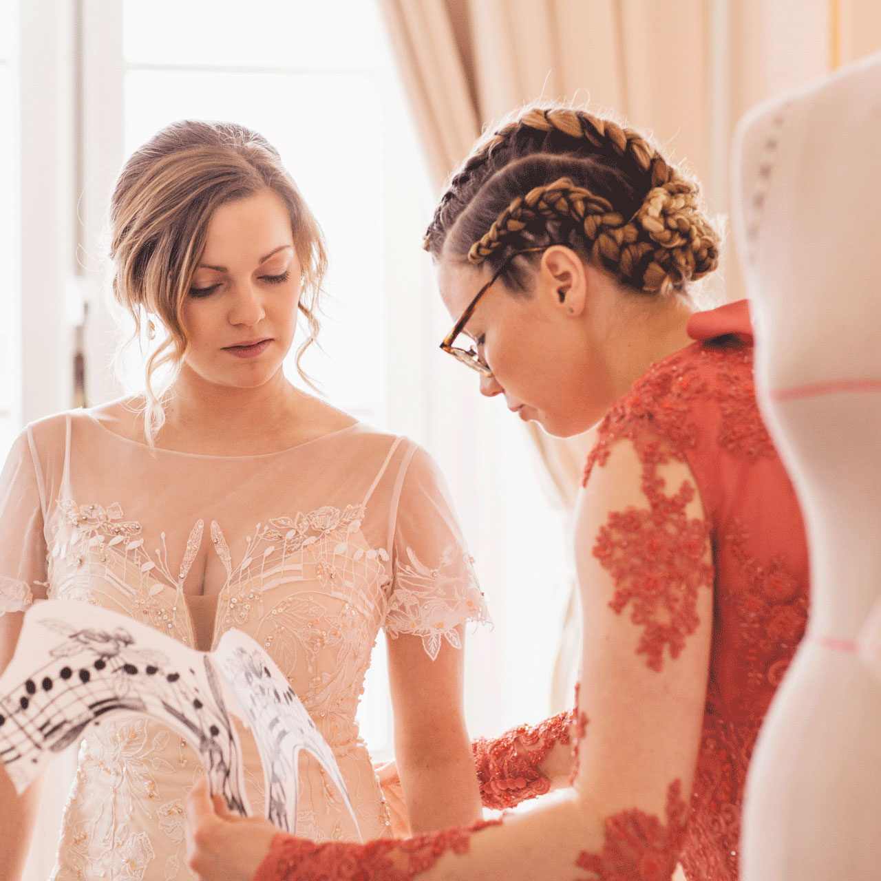 Designer sharing thoughts with the bride about adding an extra touch to the wedding dress